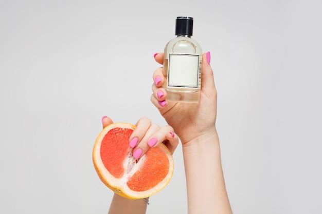 Le mani della ragazza reggono un olio o un profumo aromatico e un succoso pompelmo, su una parete bianca, vista dall'alto. profumi di agrumi di concetto, aromaterapia o cura del corpo.