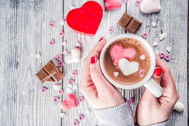 Le mani della ragazza tengono cioccolata calda con cuori di marshmallow