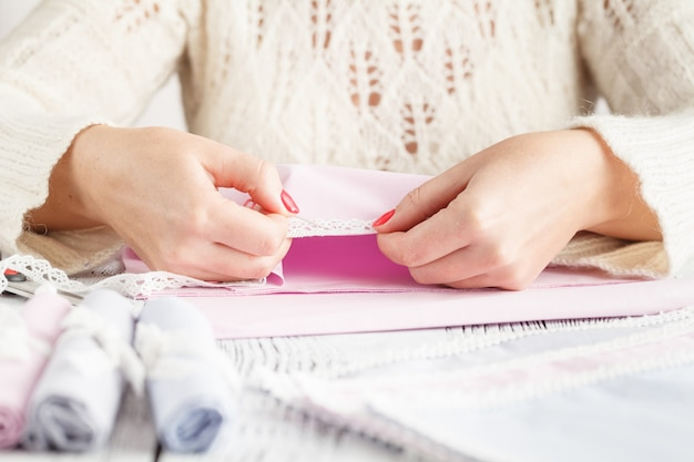 Le mani della sarta hanno fatto bei vestiti luminosi e alla moda.