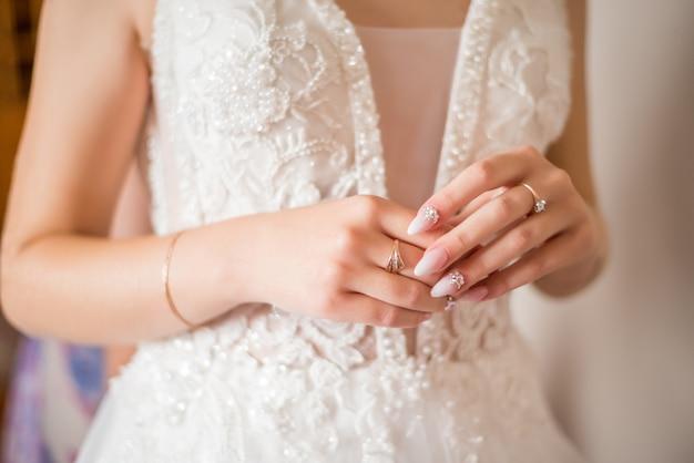 Le mani della sposa con anello di nozze d'oro con un diamante. i preparativi della sposa. mattina di nozze. gioielleria. manicure da vicino. fidanzamento. l'asola con fiori.
