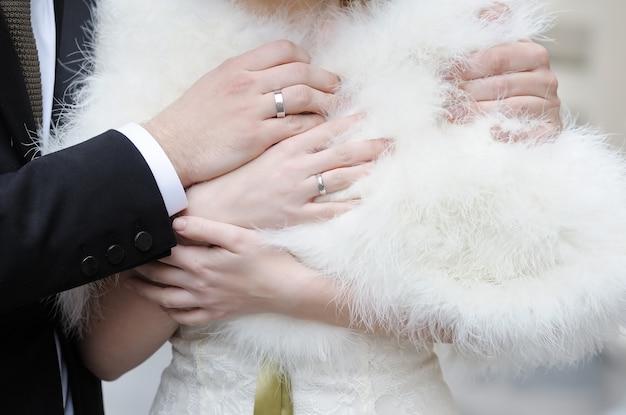 Le mani della sposa e dello sposo con le fedi nuziali