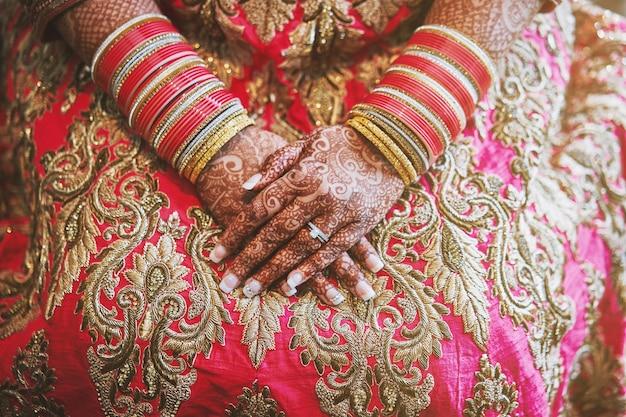 Le mani della sposa indiana con il tatuaggio menhdi e i braccialetti glitterati al polso