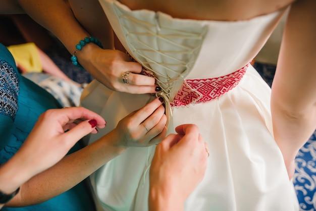 Le mani delle damigelle allacciano l'abito sul retro della sposa durante l'incontro del matrimonio