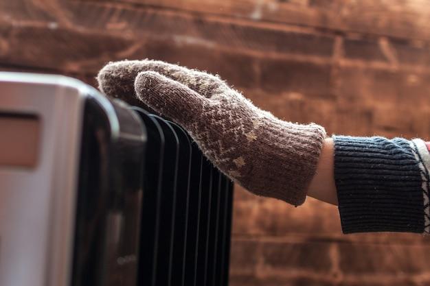 Le mani delle donne a natale, calde, guanti invernali sul riscaldamento. resta caldo in inverno, serate fredde. stagione di riscaldamento