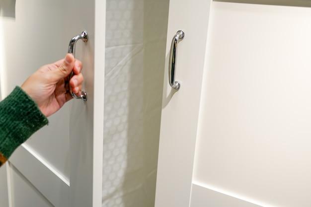 Le mani delle donne aprono la porta di legno dell'armadio dell'armadietto