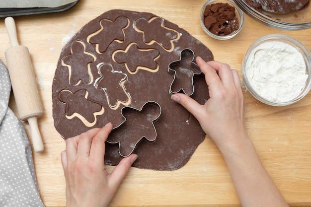 Le mani delle donne che cucinano i biscotti festivi del pan di zenzero di natale. cucinare biscotti o dessert al cioccolato.