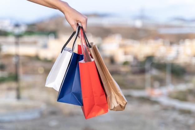 Le mani delle donne che tengono alcuni sacchetti della spesa. concetto di shopping