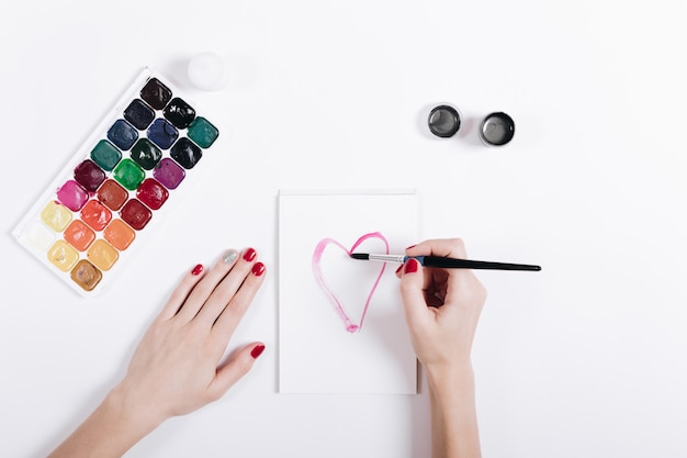Le mani delle donne con il manicure rosso hanno dipinto il cuore dell'acquerello in un taccuino