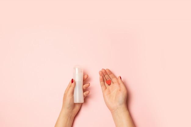 Le mani delle donne contengono grasso intimo e una forma di cuore rosso su una rosa