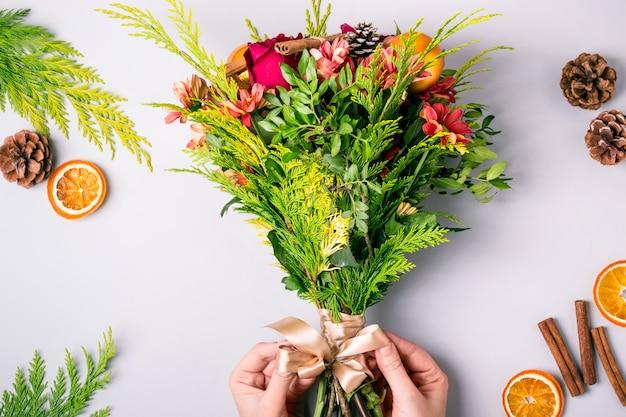 Le mani delle donne creano un bouquet natalizio invernale