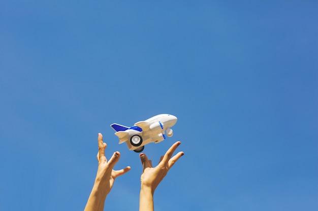 Le mani delle donne lanciano un aereo per bambini bianco e blu.