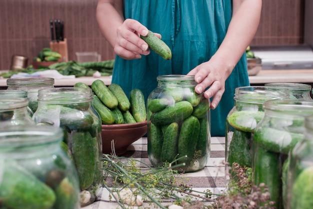 Le mani delle donne mettono i cetrioli in una lattina per l'inscatolamento