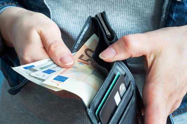 Le mani delle donne prendono denaro dai loro portafogli in euro.