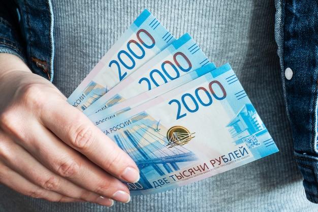 Le mani delle donne prendono rubli di denaro dai loro portafogli.