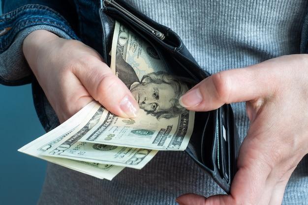 Le mani delle donne prendono soldi dai loro portafogli.