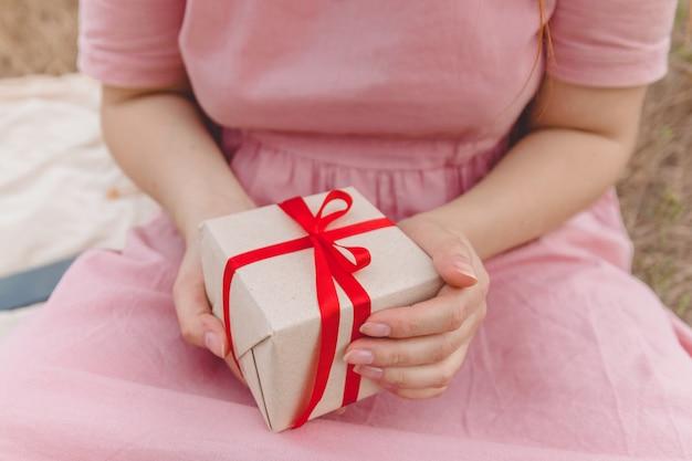 Le mani delle donne tengono il regalo di sorpresa con l'arco rosso