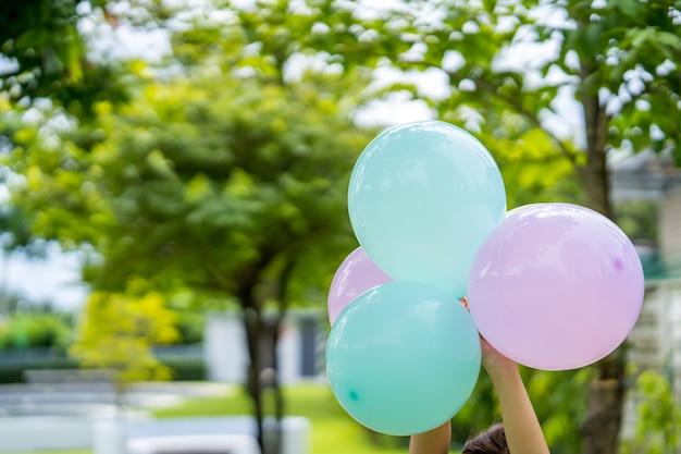 Le mani delle donne tengono un palloncino multicolore