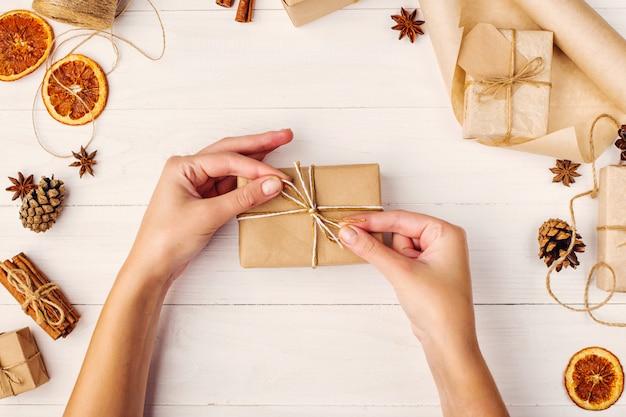 Le mani delle donne tengono un regalo di carta artigianale sullo sfondo di arancia essiccata, cannella, pigne, anice su un tavolo bianco.