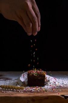 Le mani dello chef che spruzzano ciambelle dolci con zucchero a velo e setaccio per farina