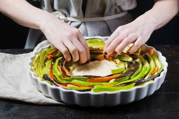 Le mani dello chef preparano la ratatouille in una pirofila.