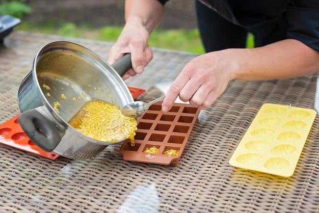 Le mani dello chef versano marmellata calda di agrumi negli stampi in silicone. marmellata di cottura.