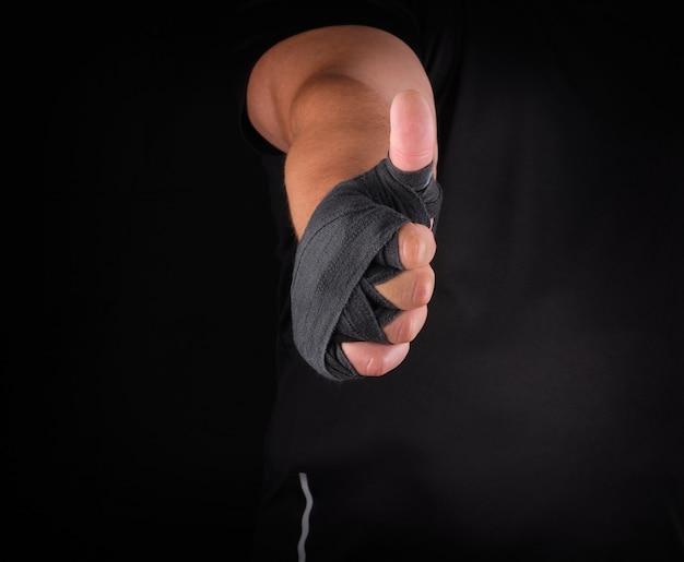 Le mani dello sportivo avvolte in un bendaggio sportivo elastico nero mostrano un segno simile