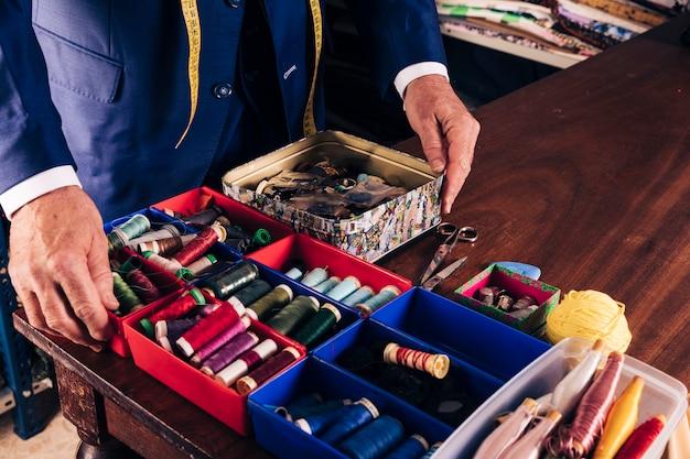 Le mani dello stilista maschio sul contenitore che contiene il tipo differente di bobine del filo sulla tavola di legno
