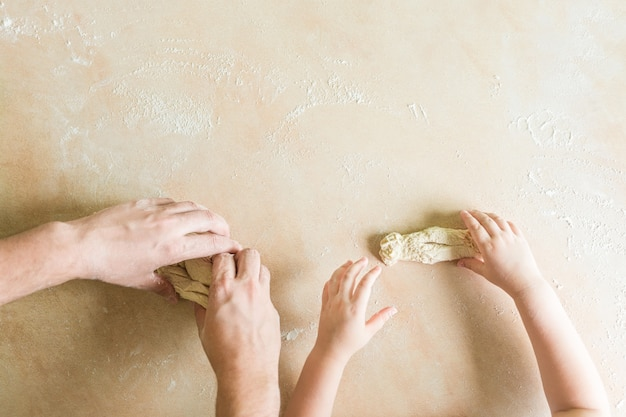 Le mani di bambini e papà producono un impasto crudo