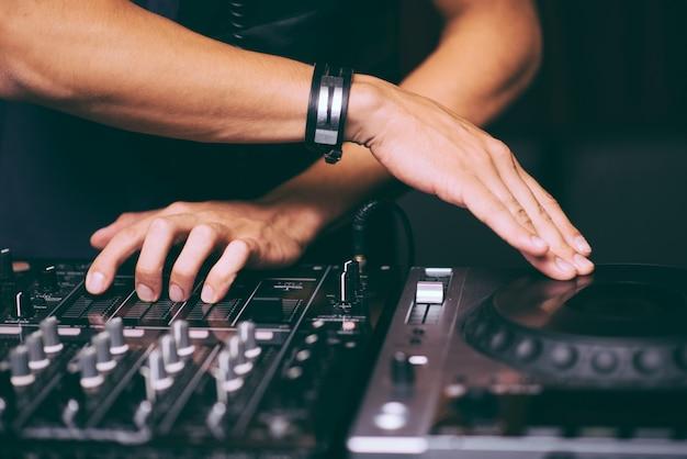 Le mani di dj controllano il primo piano del telecomando