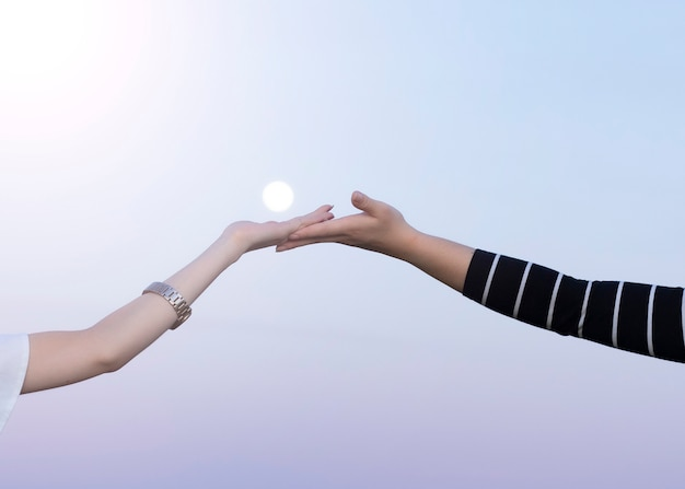 Le mani di due donne si accoppiano con la luna nel muro