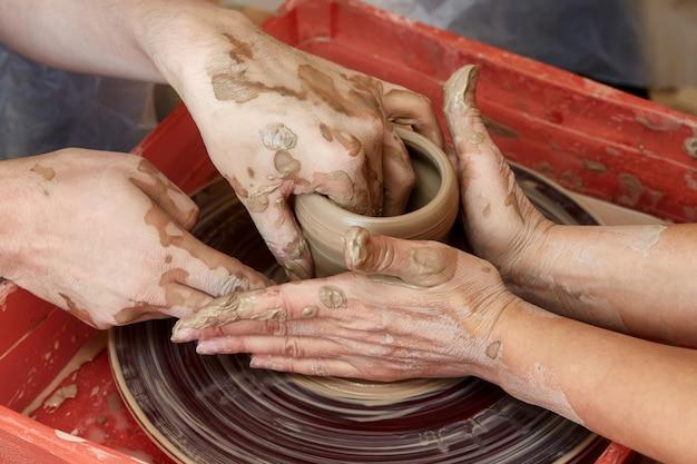 Le mani di due persone creano una pentola, il tornio da vasaio. insegnamento della ceramica
