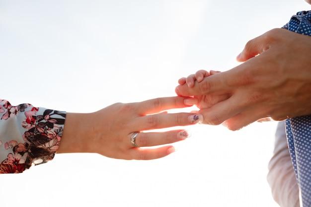 Le mani di mamma e papà tengono la mano del bambino