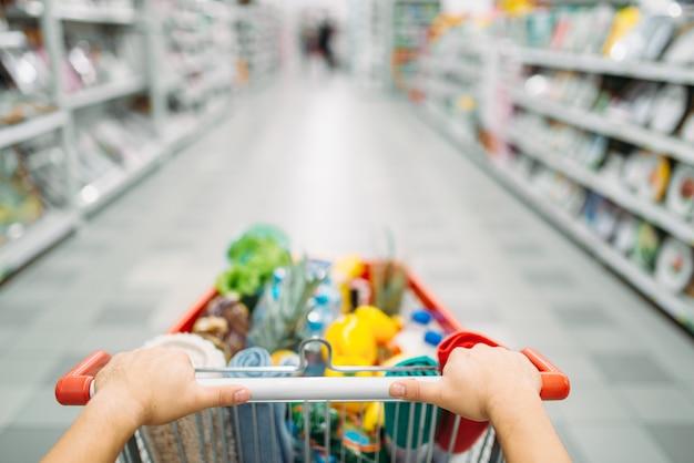 Le mani di persona di sesso femminile trascinano il carrello pieno di merci in un supermercato, a fare la spesa. cliente in negozio, acquirente nel mercato, concetto di acquisto