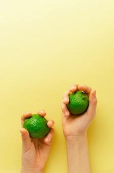 Le mani di qualcuno tengono due lime verdi