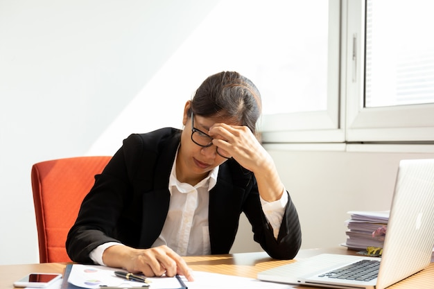 Le mani di riposo della donna di affari sulla testa con gli occhi si chiudono allo scrittorio del lavoro in ufficio.