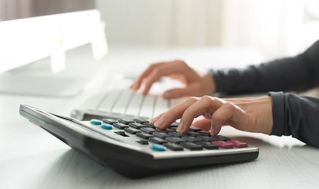 Le mani di un analista finanziario contano su una calcolatrice e lavorano su un computer. donna ragioniere sul posto di lavoro.
