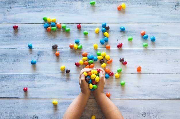 Le mani di un bambino che tengono la pila di caramelle colorate