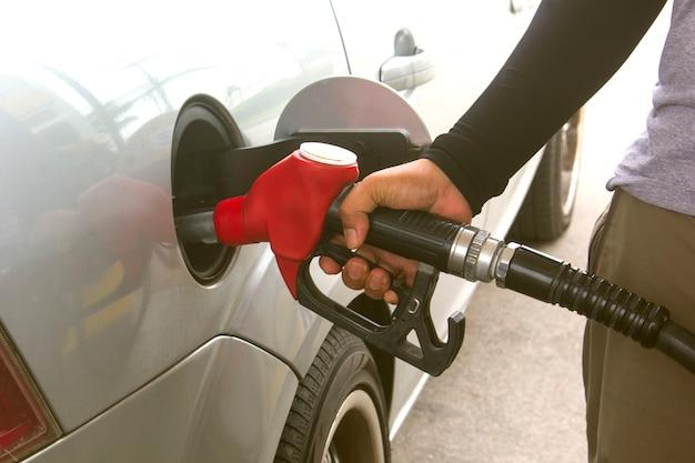 Le mani di un giovane fanno rifornimento di carburante alla macchina.