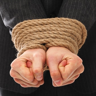 Le mani di un giovane legato con la corda