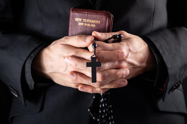 Le mani di un prete cristiano vestite di nero con in mano un crocifisso e il libro del nuovo testamento. persona religiosa con perline bibbia e preghiera, immagine scura.