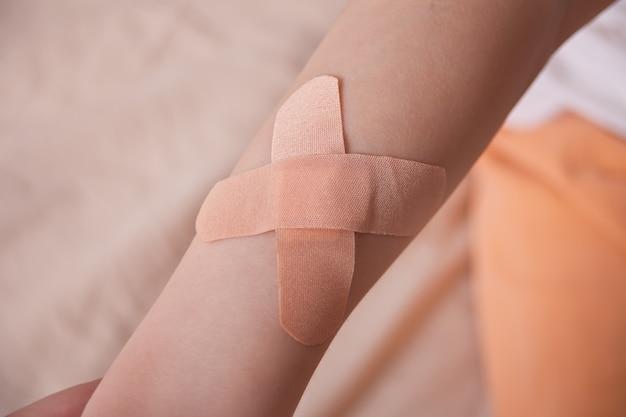 Le mani di un ragazzo con una chiazza di adesivo attaccata alle sue mani.