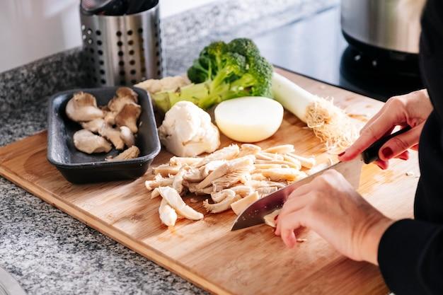 Le mani di una donna che tagliano funghi e cavolo e porri di cipolla di verdure in una cucina