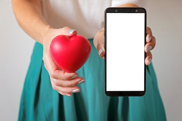 Le mani di una donna che tengono un simbolo del cuore sulla pancia e sullo smartphone. domanda di salute della donna, ginecologia