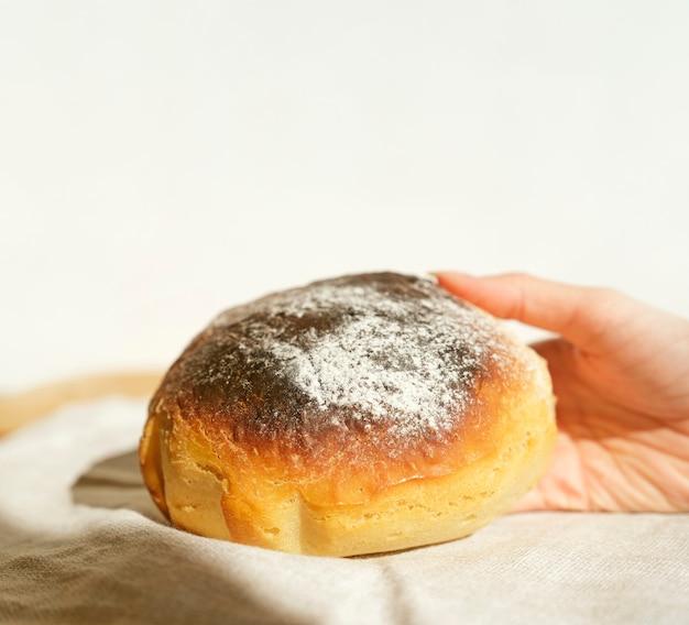 Le mani di una donna che tiene pane appena sfornato a casa si chiudono. sfondo bianco.