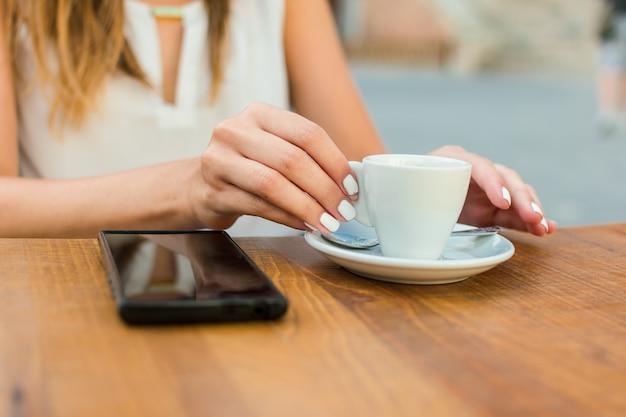 Le mani di una giovane donna stanno tenendo una tazza di caffè sulla terrazza di un pub