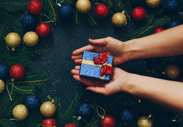 Le mani di una ragazza in possesso di un regalo di natale su uno sfondo nero