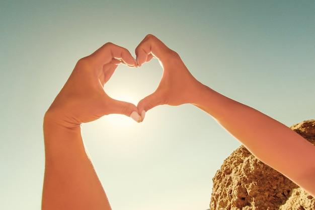 Le mani femminili a forma di cuore contro il cielo passano i raggi del sole.