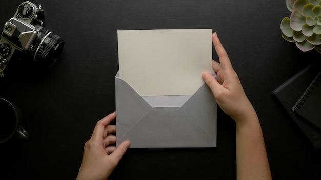 Le mani femminili aprono la cartolina d'auguri con la busta grigia sulla scrivania scura con la macchina fotografica e le decorazioni