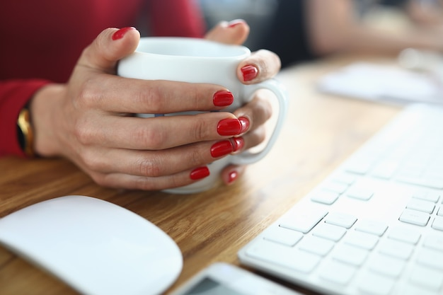 Le mani femminili con il manicure rosso tengono la tazza bianca sul tavolo di lavoro