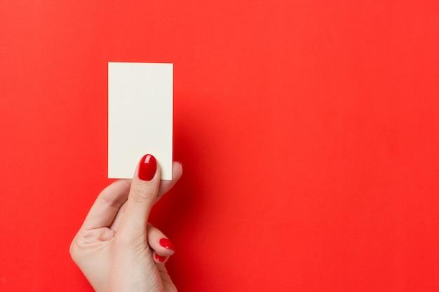 Le mani femminili con il manicure rosso tiene un biglietto da visita in bianco bianco